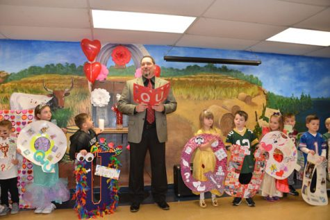 The Pre-K students stand dressed as queens and quarterbacks during the wedding.