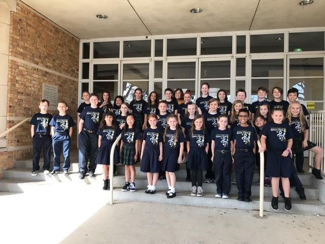 MCA Honor Choir stops and poses for a picture outside of Scofield School.