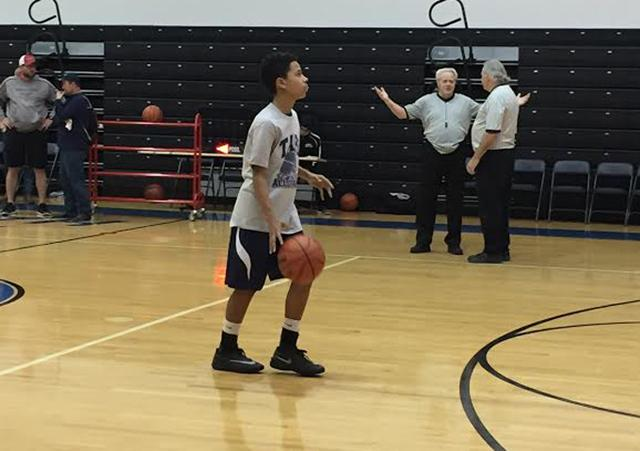 Asa Miller practices to take a shot while warming up for the game.
