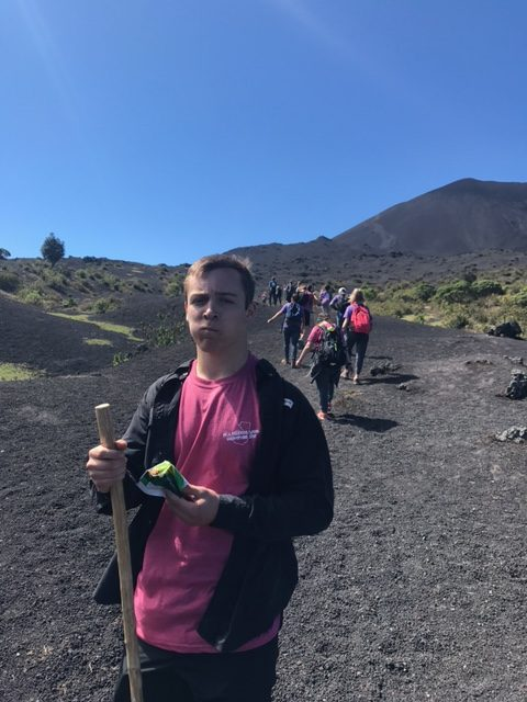 Will Harrell eats a dried mango as he hikes a volcano.