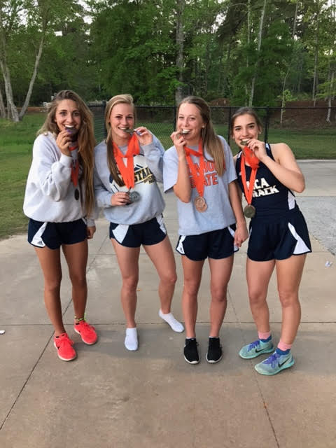Freshman, Wave Frisbie, Sophomores, Kate Witte and Elyse Mead, and Senior Katie Dossey pose for a cute picture with their medals they won from the 4x4 Relay.