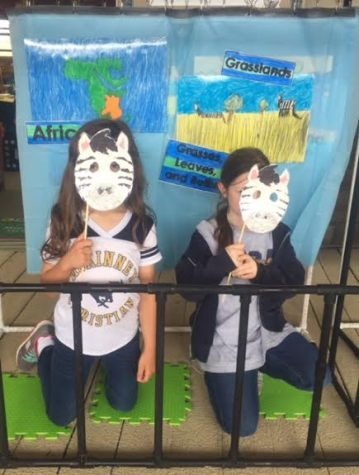 Two first grade students hold up the masks they made for the talking zoo.