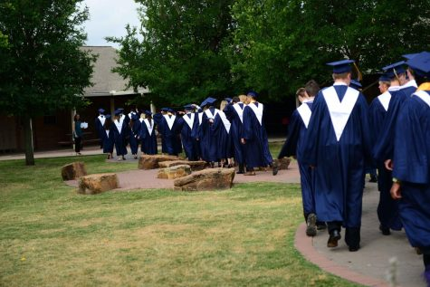 The Seniors walk down the main path of the courtyard towards the Lower and Middle School deck.