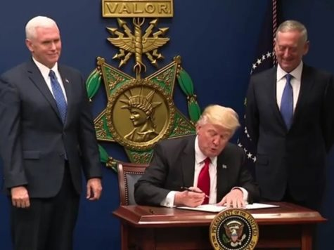 President Trump signs a bill with Vice President Pence and Secretary of Defence Mattis looking on.