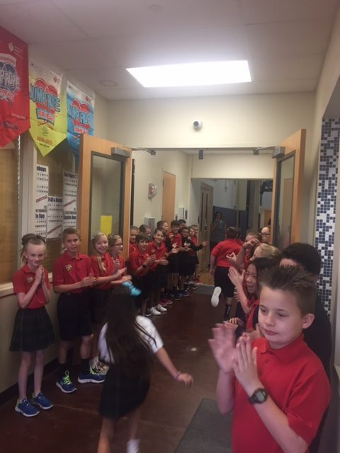 5th graders line the halls to welcome the lower school to chapel.