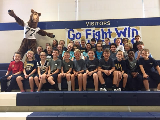 The fifth graders gather together to take a group picture at the pep rally.