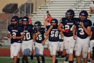 Some of the MCA football starters head out to the field ready to play.