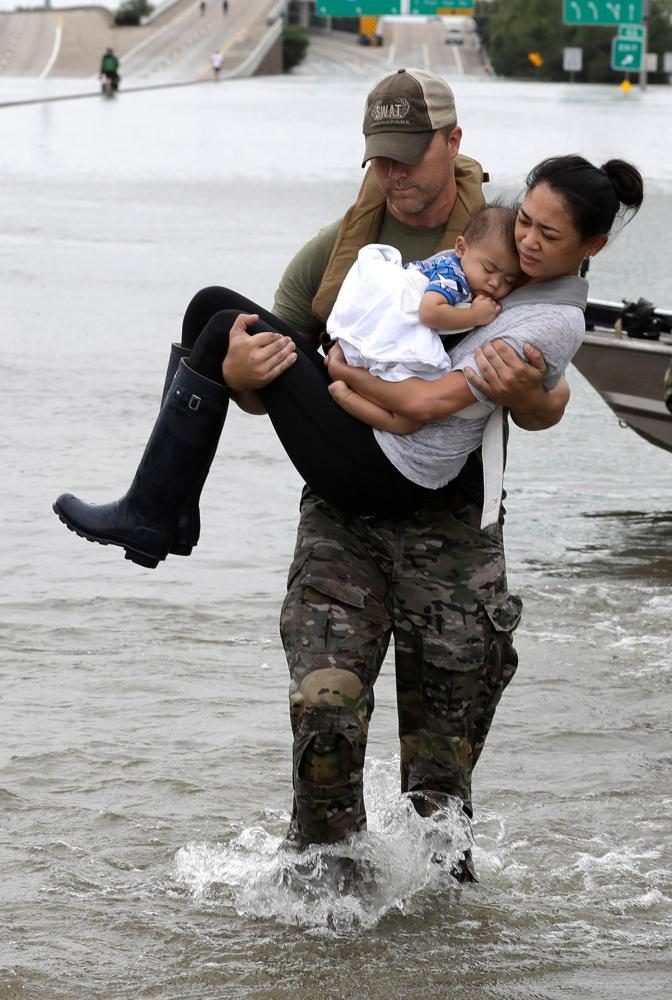 A Texan carries a woman and her child who had been stranded with the rising flood waters trapping them in their house.