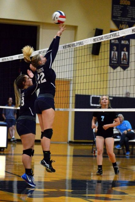 Aby Beck and Courtney Martin jump to get a block against Waco Riecher.