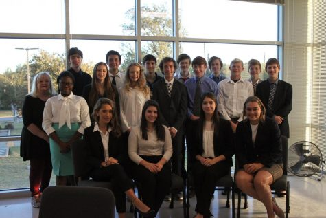 Upper School Debate team poses for a picture at a tournament.