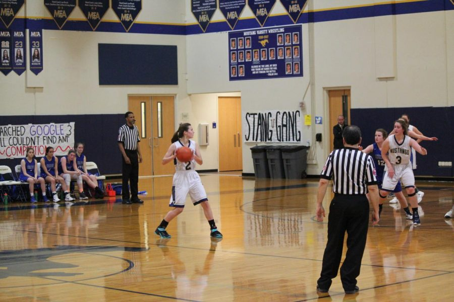 Abigail Moore takes the ball down the court and looks for a pass.