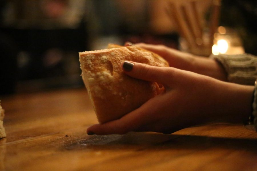 A girl breaks bread around the table.