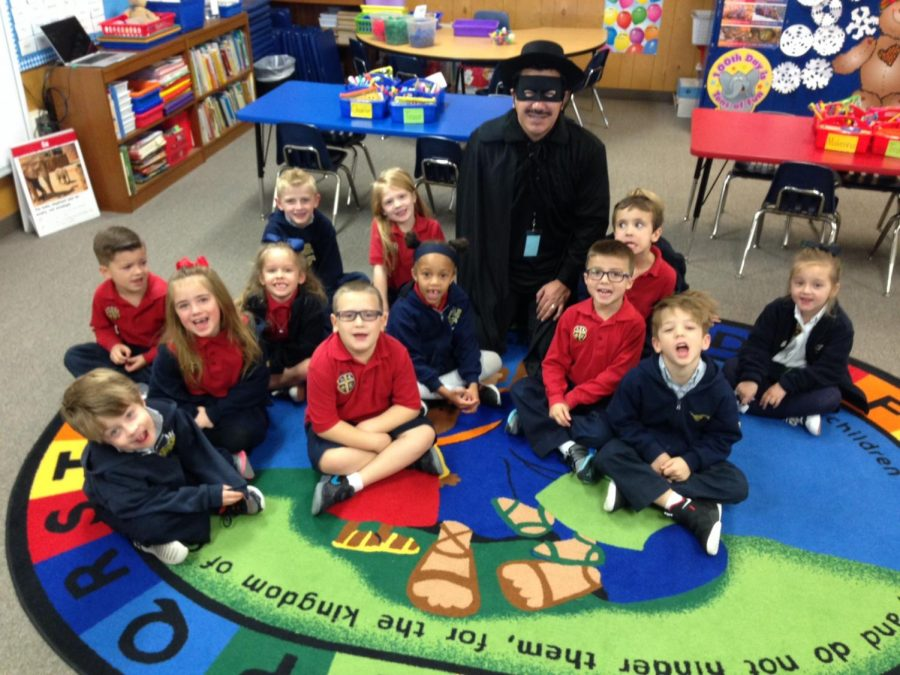 Mrs. Hamilton's kindergarten class poses with Zero Hero as they count out their collection of 100 items that they brought.