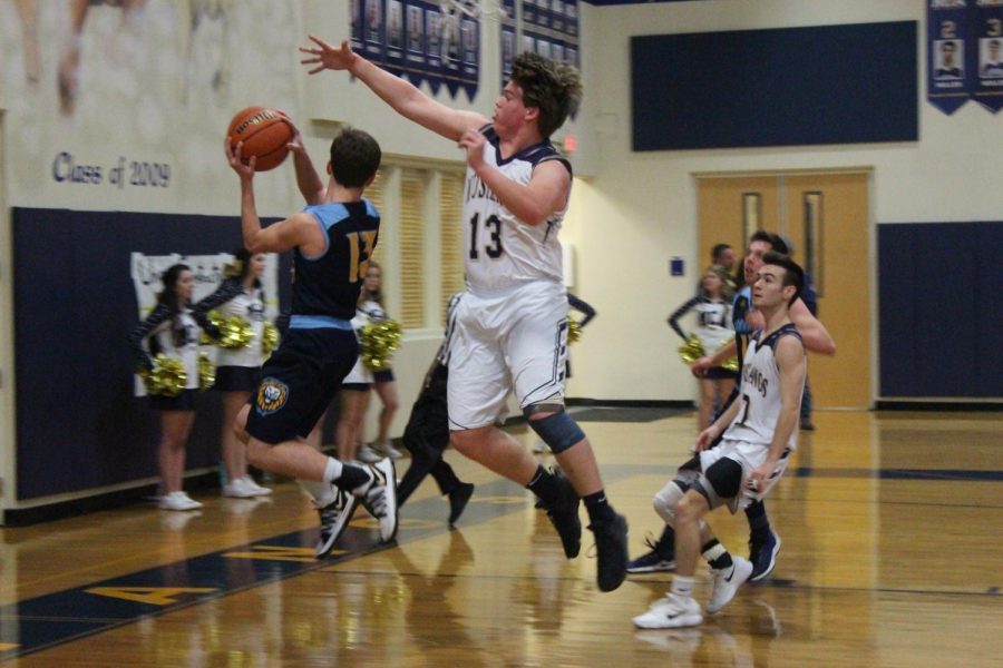 Will Baxter, junior, blocks a shot by Coram Deo guard.