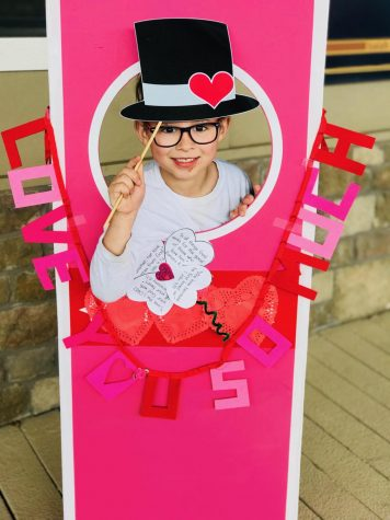 First grade students take Valentines Day pictures in a crafty photo booth.