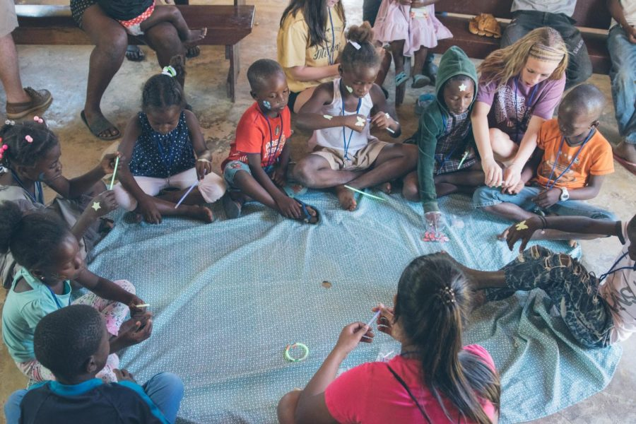 Junior, Katherine Hines, sits with children from the Batey to make crafts