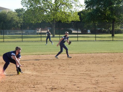 Third baseman Allie Smith fields the ball and throws the runner out at first.