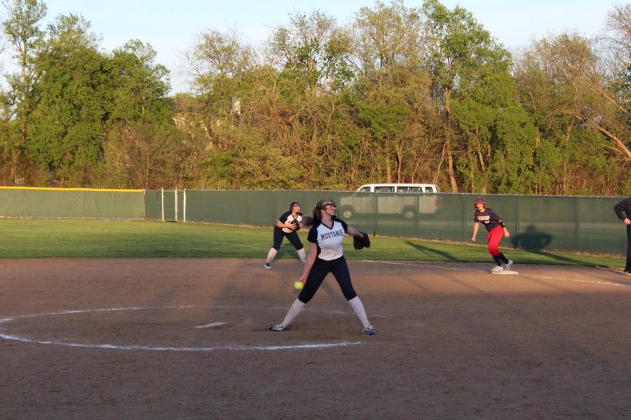 Sophomore Jodee Newland throws a fast pitch to the opposing team to strike the batter out.