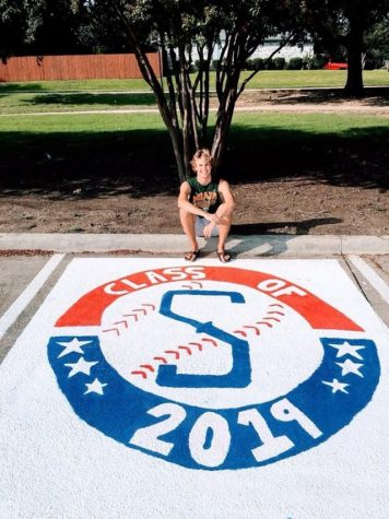 Senior Sam Utzig takes a picture after finishing painting his parking spot.