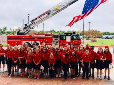 The Lower School Honor Choir groups together to take a picture in front of the fire truck.