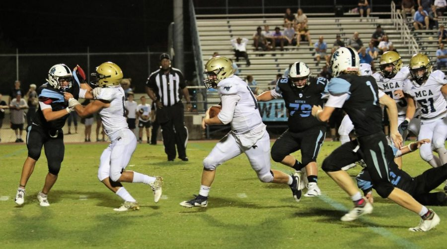 Senior Captain Will Baxter carries the football through the defense while Levi Miller blocks for him.
