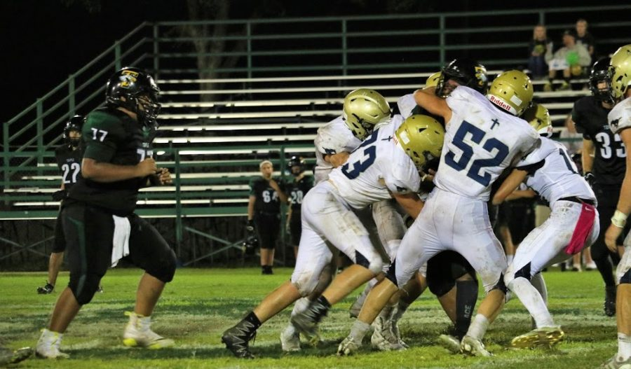 Senior Captain Caleb Doyle  leads a group of Mustangs in a tackle.