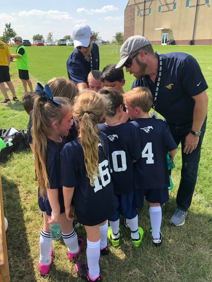 The first grade soccer team is huddling up before the game.