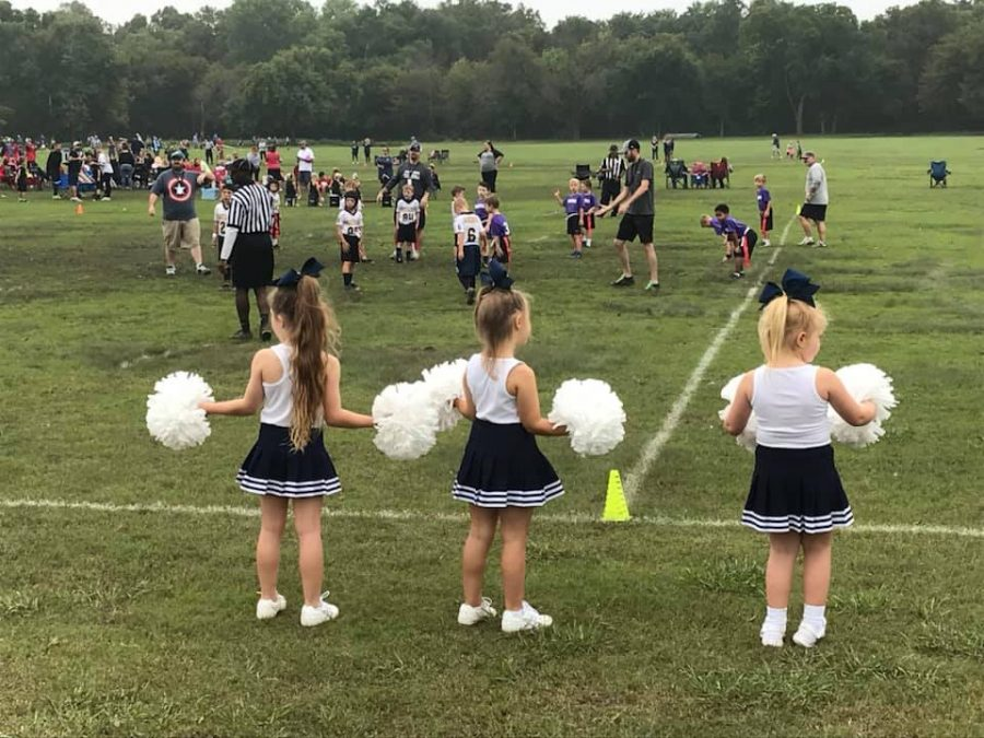 The Lil Stangs football team plays in a muddy game while the Lil Stangs cheerleaders cheer them on.