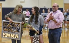 Senior Emma Lowes laughs with her family as she is recognized at senior night.