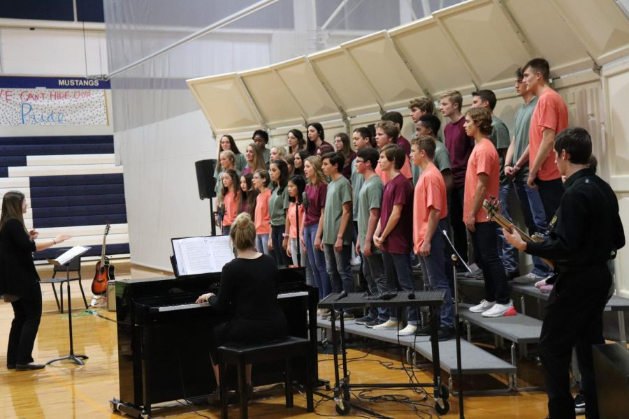 The Upper School Choir singing dressed in their Fall colored shirts.