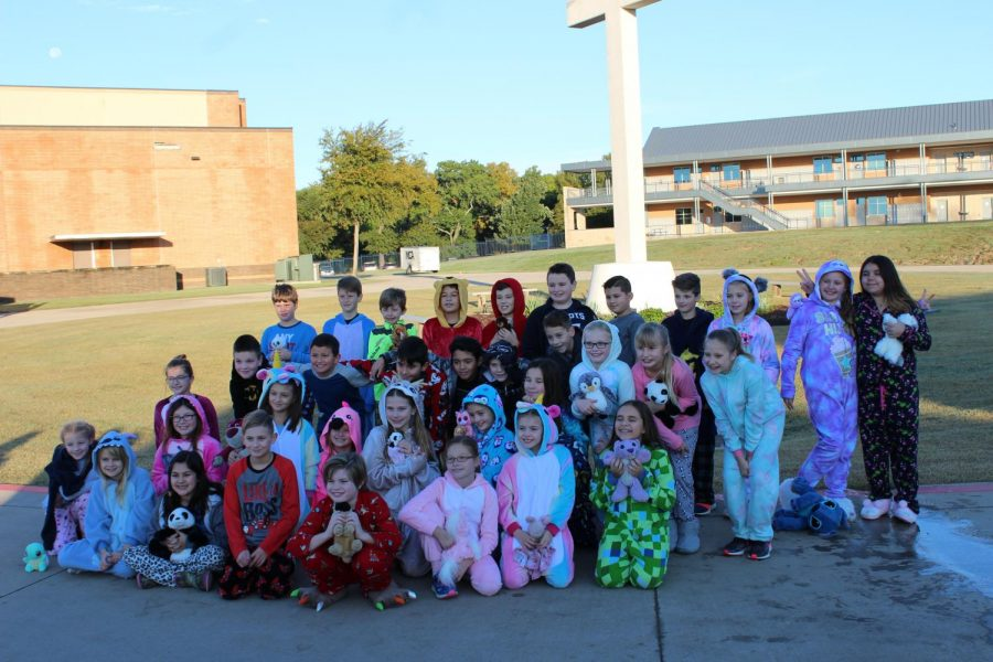 The fourth grade class finish the parade with a picture in front of the cross.