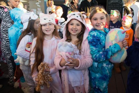 A few second grade girls pose for a picture together with their stuffed animals.