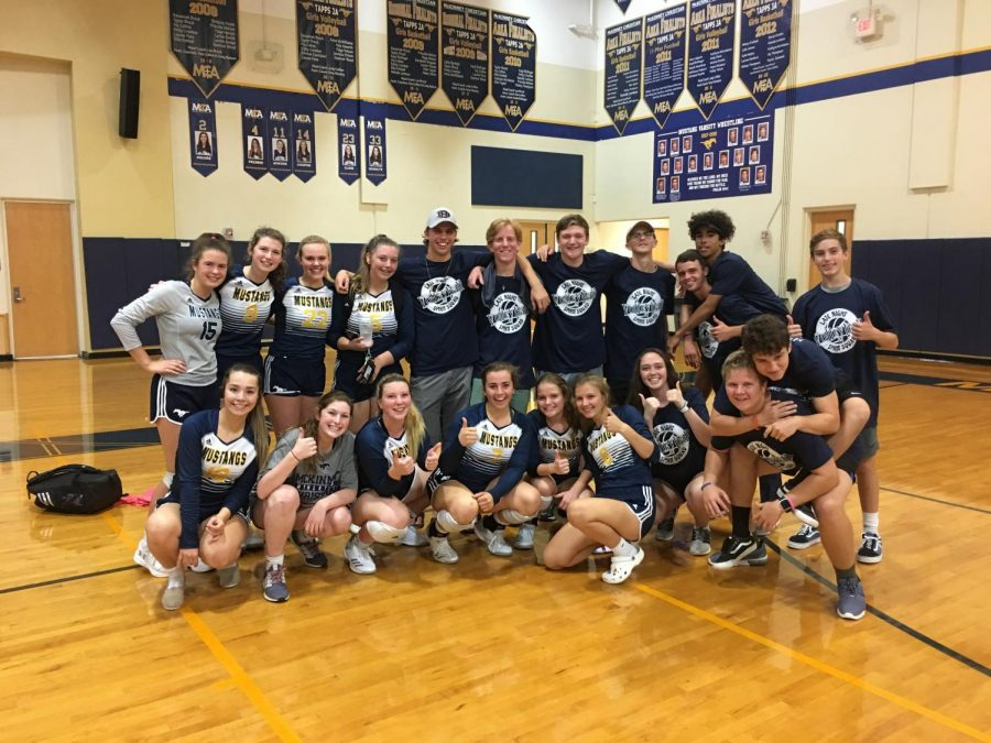 Varsity volleyball celebrates a big win with the Late Night Spirit Squad in their new t-shirts.