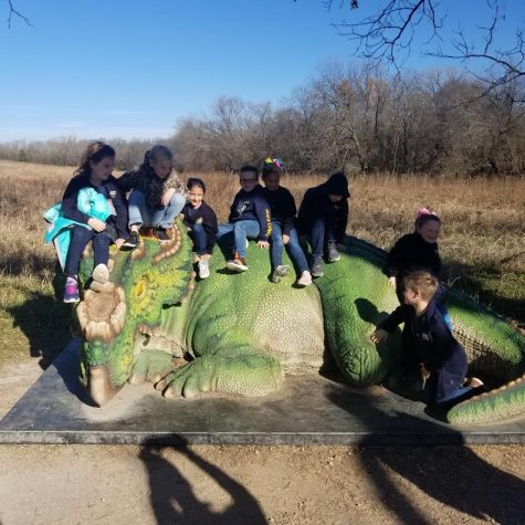 Second graders sit on top of a dinosaur statue.
