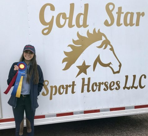 After finishing the competition Cueva stops by her horse trailer to pose for a picture with her ribbons she won.