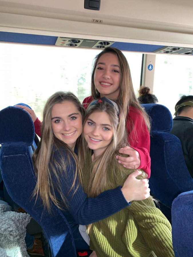 After getting a seat on the back of the bus, seniors Emma Thompson, Remi Wilson, and Naty Tubiolo smile for a picture.