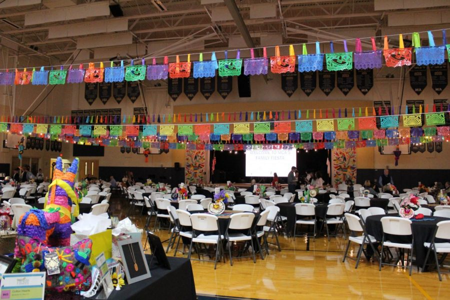 A view from the back of the gym of all the decorations and tables at the fiesta.