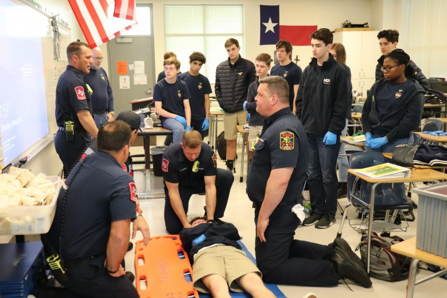 The class is taught by Station 2 on how to gently place an injured person onto a backboard.