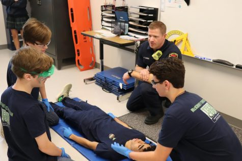 A few sophomores listen to P. Zurek as he explains how to properly care for an injured person.