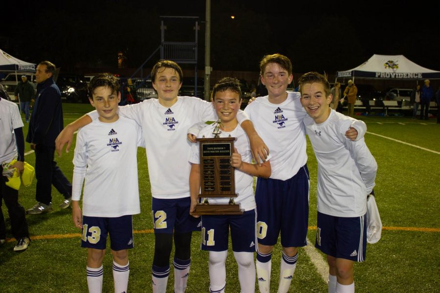 Five former Lil Stangs soccer players hold up their championship trophy after winning the TAPS soccer championship last night.