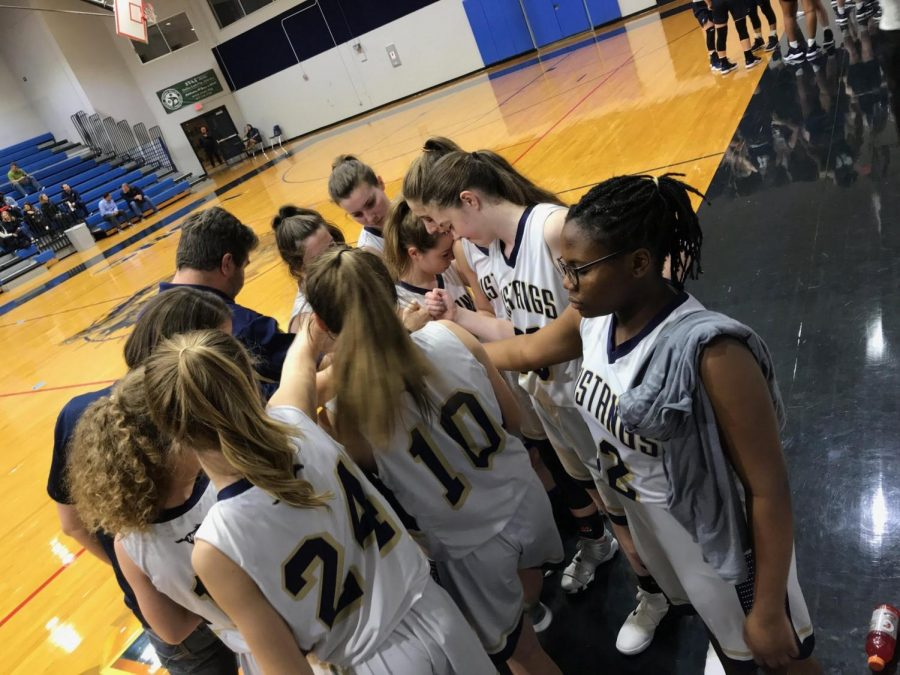 The+Varsity+Basketball+team+says+a+prayer+before+starting+the+game.