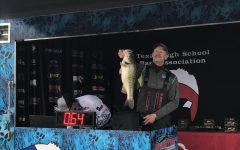 Boat Captain Jon David Cross holds up his winning fish, as the crowd cheers in excitement.
