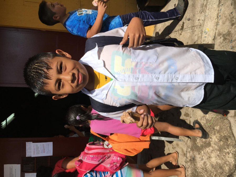A student in Zapote poses to get a picture taken at the fiesta with his ice cream.