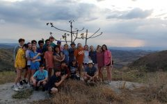 The group poses for a picture in front of a scenic view of the mountains