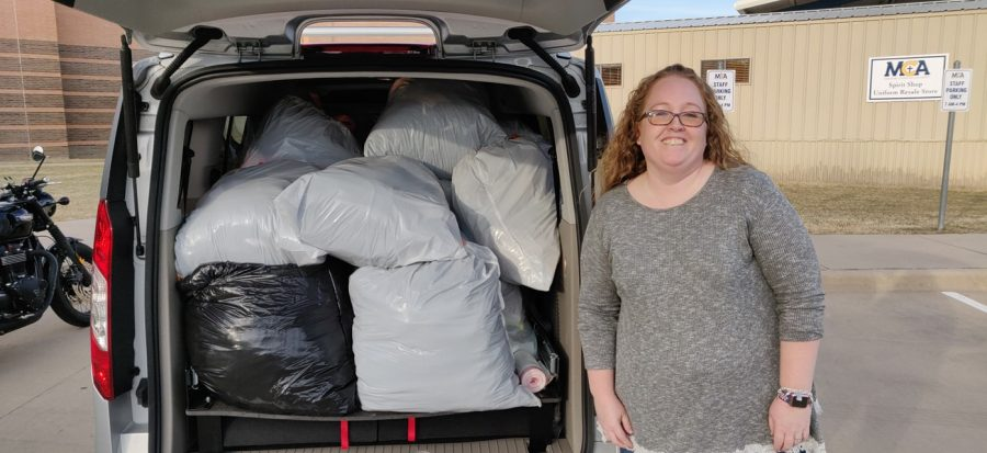 Kristin Urban stands beside some of the 400 pounds of clothing that were donated from MCA.