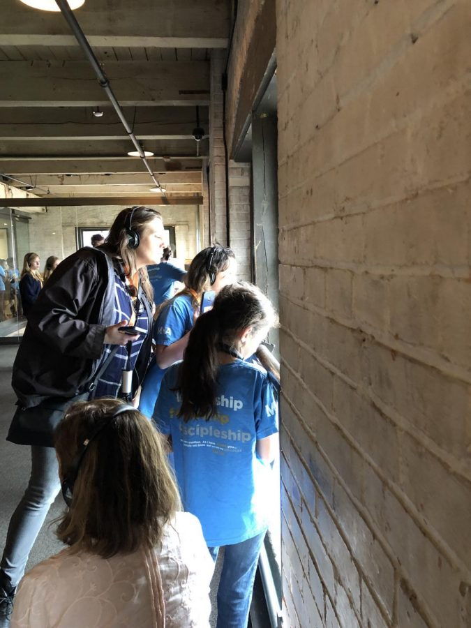 Karen Chastain and a few girls look out the window at the Sixth Floor Museum.
