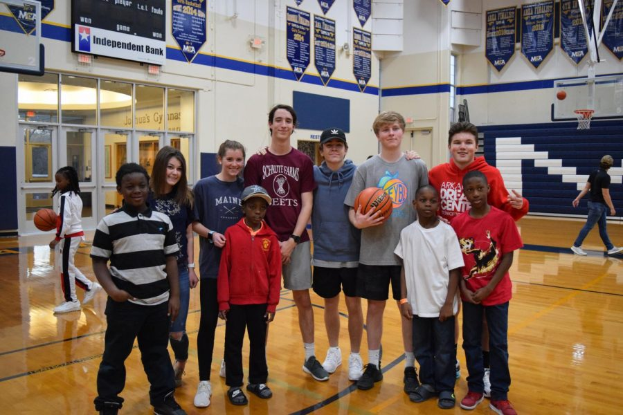 Seniors, Lauren Shackelford, Juliana Roller,Mason Lee, Trey Faulkner, Kade Stephens, and Dylan King pause a basketball game to take a picture with kids from the Dream Center.