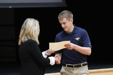 Christian Simonsen shakes Mrs. Smith's hand as he accepts his NHS certificate.