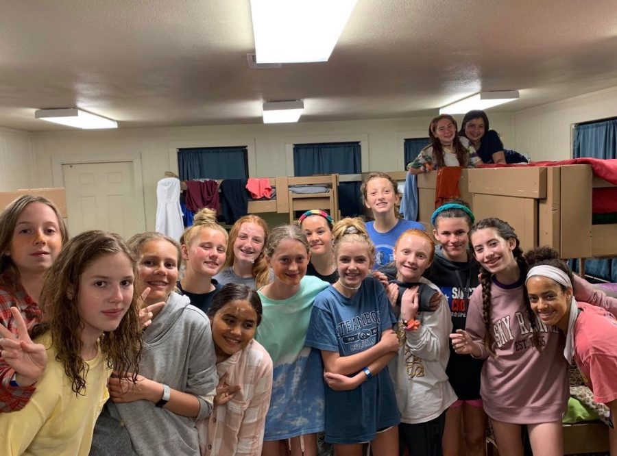 A group of 7th grade girls take a picture while hanging out in the cabin.