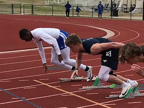 As the gun goes off, junior Aaron Phillips starts to push off of the blocks to race in the 100m dash.